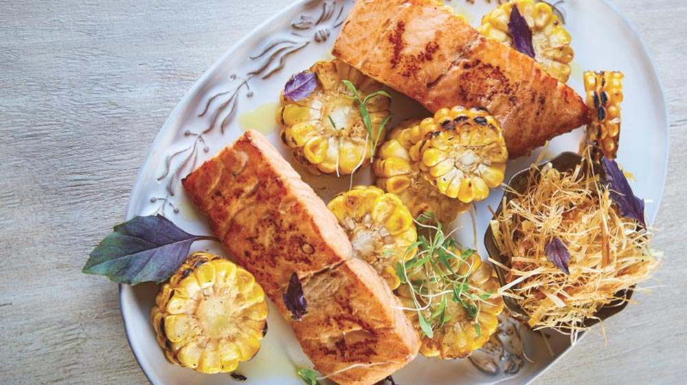 salmón con elote quemado y poro frito