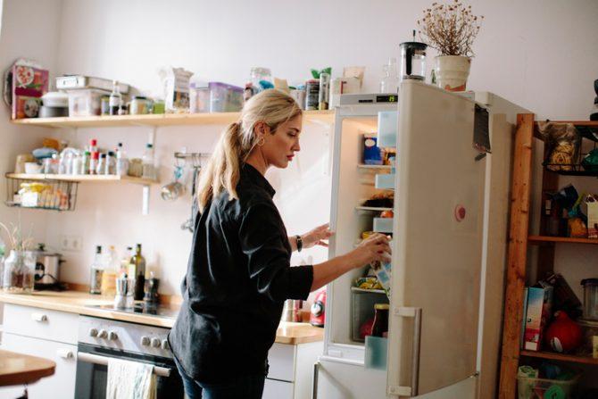 mujer viendo interior de refrigerador en casa