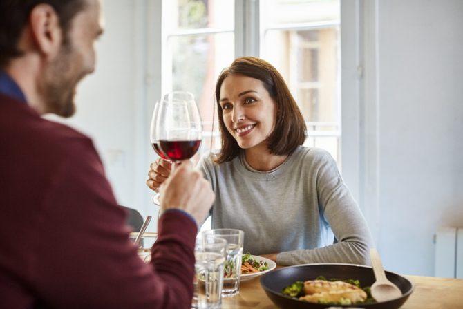 pareja joven bebiendo vino tinto en su cocina